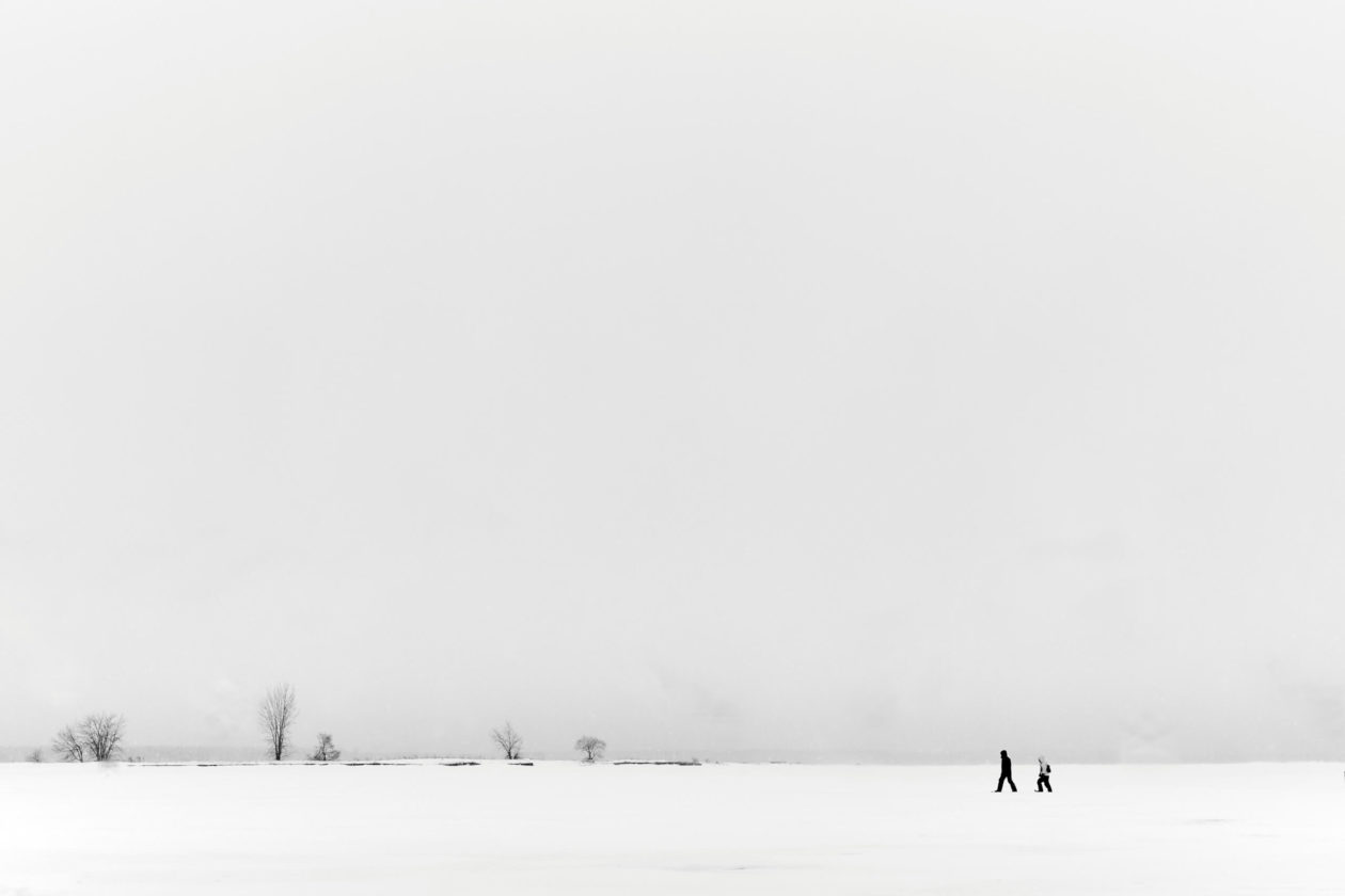 Canon 5D Mark iii with ef 50mm 1.8 - Landscape Photography - Two people walking on a frozen river at Rene Levesque Park Montreal Quebec